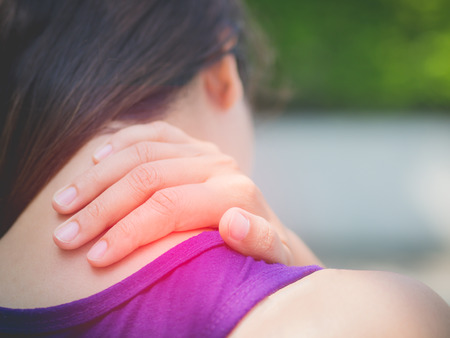 Closeup athletic young woman touching her neck by painful injury, over a nature background. Sport injuries concept.
