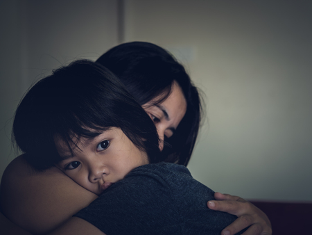 Mother and child, cute little boy resting on her mother's shoulder. Young mother holding her sad boy at home. Stockfoto