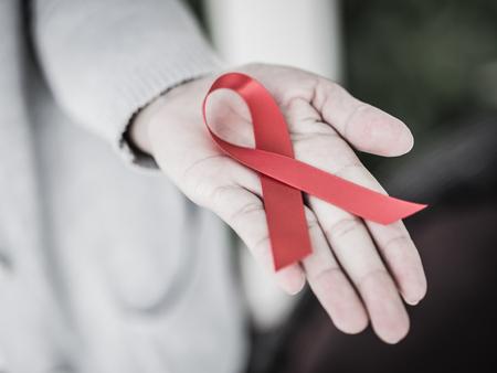 世界エイズ日アウェアネス リボン、赤リボン HIV を持つ女性の手のレトロなスタイル。 薬と健康管理の概念。 写真素材