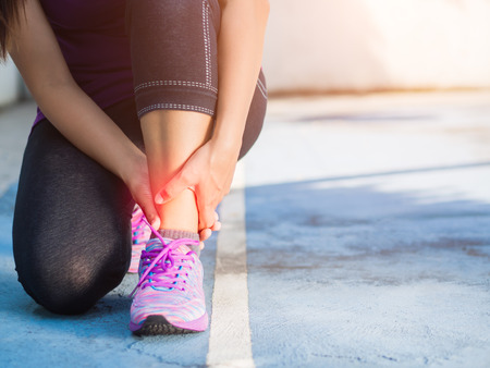 Young woman suffering from an ankle injury while exercising and running. Sport  excercise concept. Stock Photo