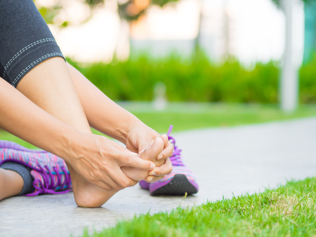 Young woman massaging her painful foot from exercising and running Sport  and excercise concept. Stock Photo