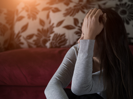 Closeup portrait of sad young woman sitting by sofa at home.