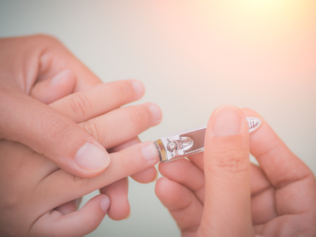 Family activity, soft focus of mother hand cut nails for kid by using nail clipper. Stockfoto
