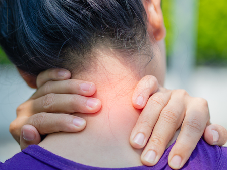 Athletic young woman touching her neck by painful injury, over a nature background. Sport injuries concept.
