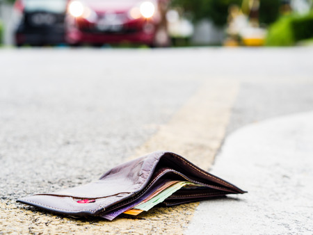 Lost leather wallet with money drop on the road , lost money concept, copy space on top.