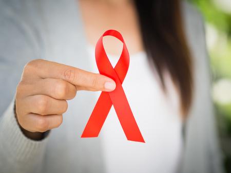 확대 사진 여자 손을 잡고 빨간색 리본 에이즈, 세계 에이즈 하루 인식 리본입니다. 의료 및 의학 개념입니다.