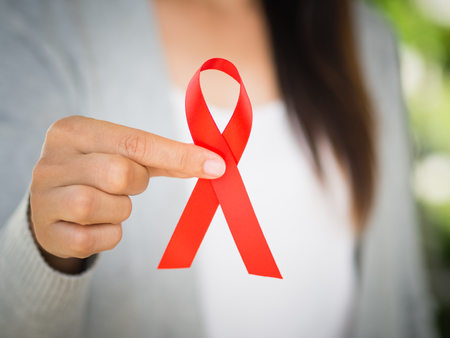 Closeup woman hand holding red ribbon HIV, world AIDS day awareness ribbon.  Healthcare and medicine concept. Banque d'images