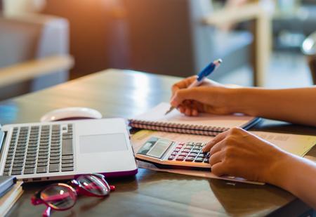 Femme travaillant avec calculatrice, document d'entreprise et ordinateur portable Banque d'images - 84599811