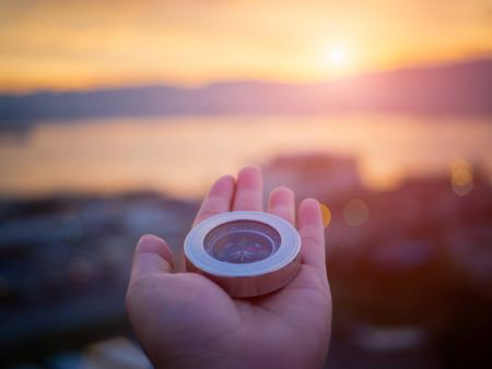 クローズ アップ手山と夕日の空の背景とコンパス。 写真素材