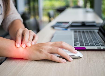 컴퓨터를 사용 하여 그녀의 손목 통증을 들고 근접 촬영 여자. Office syndrome 직업병에 의한 손의 통증.