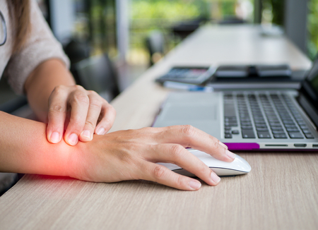 Closeup woman holding her wrist pain from using computer. Office syndrome hand pain by occupational disease. Foto de archivo