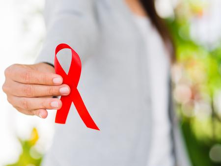クローズ アップ世界エイズ日アウェアネス リボン、赤リボン HIV を持つ女性の手。 薬と健康管理の概念。