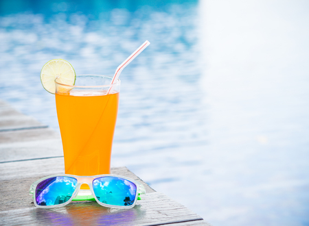Sunglasses with orange juice and a piece of lemon at the side of swimming pool. Vacation, beach, summer travel concept Stock Photo