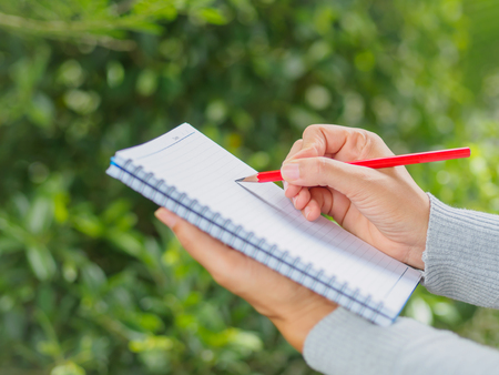 Woman hand with red pencil writing on notebook in agriculture garden.