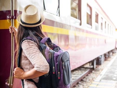 Nahaufnahme eine schöne Frau mit Rucksack auf den Schritten des Personenzugs. Reise- und Ferienkonzept. Standard-Bild