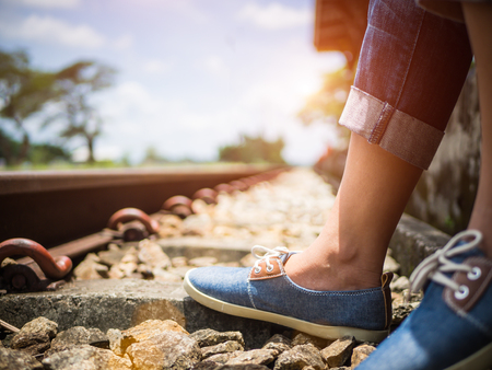 Closeup woman feet in blue sneakers sitting by the railway. Vacation and travel concept. Stock Photo