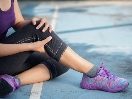Young woman suffering from an ankle injury while exercising and running. Sport exercise injuries concept. 스톡 콘텐츠