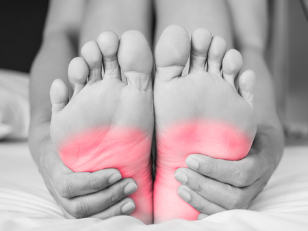 woman massaging her painful foot, red hi-lighted on pain area Stock fotó