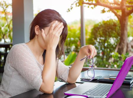 De vermoeide bedrijfsvrouw heeft hoofdpijn van bureausyndroom na urenlange werk op de computer. Stockfoto - 85969950