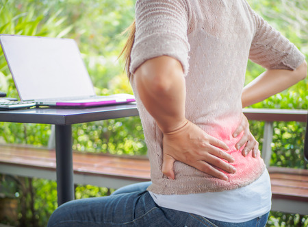 Closeup woman with hands holding her back pain. Office syndrome and Health-care Concept. Stock Photo