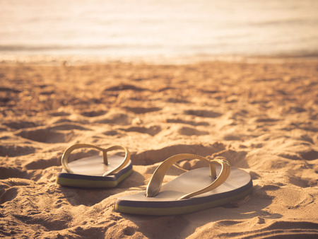 Soft focus at pair of flip-flops on the white sand beach with clear blue sea and sky,warm and vintage tone. Sad and hopeless concept.