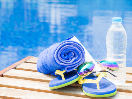 flip flops: flip flops, sunglasses and blue towel at the side of swimming pool. Vacation, beach, summer travel concept