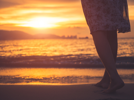 Silhouette of woman walking alone on the beach during sunset.   Emotion, sad woman concept. Stock Photo