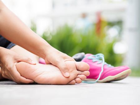 Close-upvrouw die haar pijnlijke voet masseren terwijl het uitoefenen. Sportblessure concept uitvoeren. Stockfoto