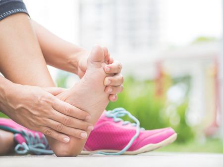 확대 사진 여자 운동하는 동안 그녀의 고통스러운 발을 마사지입니다. 스포츠 부상 개념을 실행합니다. 스톡 콘텐츠