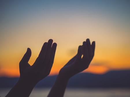 クローズ アップ女性の手が夕日を背景に神からの祝福のために祈って。コンセプトを願ってください。