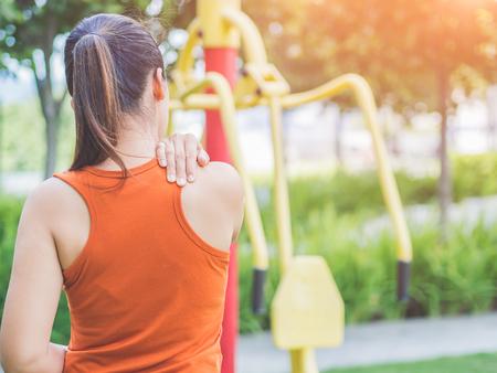 De jonge Aziatische vrouw voelt pijn op haar hals en schouder terwijl het uitoefenen, gezondheidszorgconcept. Stockfoto