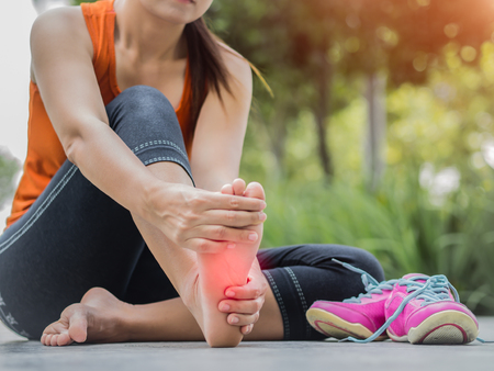 rupture: Soft focus woman massaging her painful foot while exercising.   Running sport injury concept.