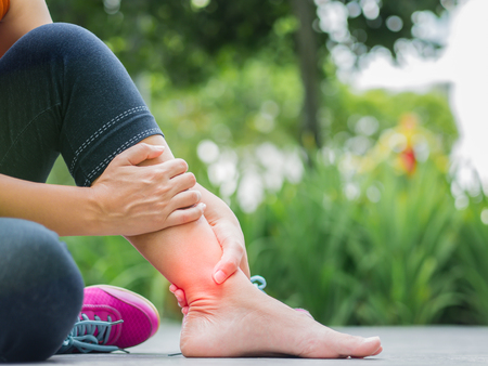 Woman suffering from an ankle injury while exercising.  Running sport injury concept. Stockfoto