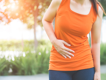 tired: Sport girl have stomach pain after jogging work out in park. Health care concept.