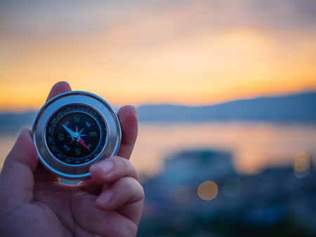 Closeup hand holding compass with  mountain and sunset sky background.