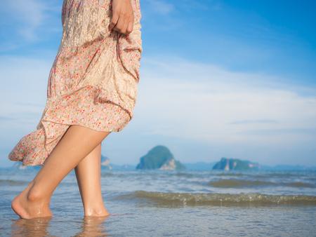 砂浜の上を歩く女性。女性の足のクローズ アップの詳細。概念をステップします。 写真素材