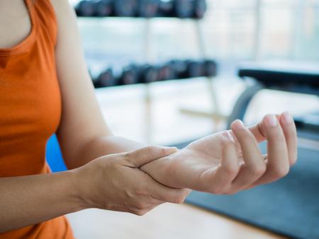 Junge Frau, die ihr Handgelenk nach dem Ausarbeiten oder verletzten Hand während der unvorsichtigen Sportübung mit Eignungsausrüstungshintergrund massiert