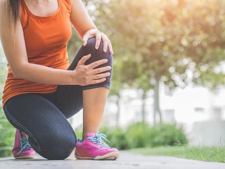 Runner sport knee injury. Woman in pain while running in the garden. Standard-Bild