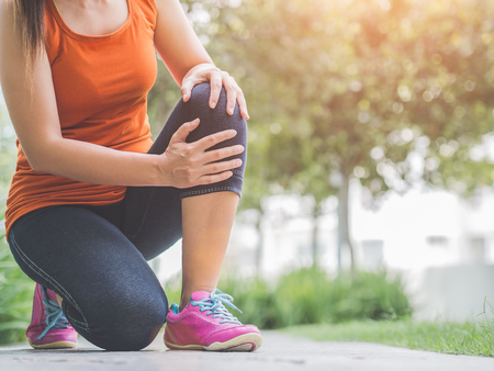 Runner sport knee injury. Woman in pain while running in the garden. Stockfoto