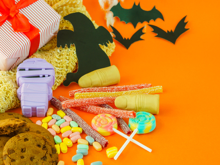 Happy Halloween decorations and candies on orange background.