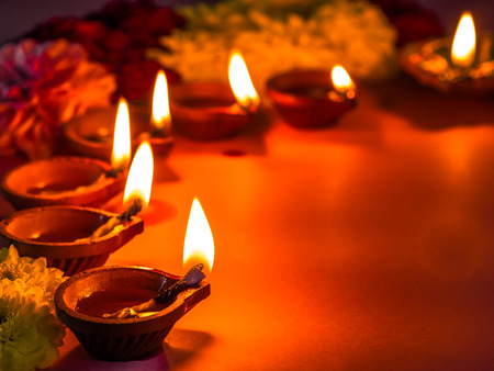 Traditional clay diya lamps lit with flowers for Diwali festival celebration. Stockfoto