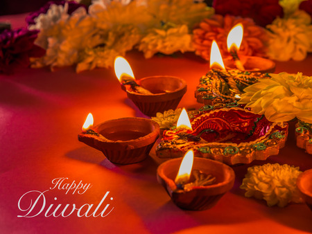 Colorful traditional clay diya lamps and flowers, with selective focus. Stock Photo