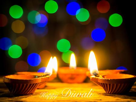 Happy Diwali - Diya lamps lit with bokeh background during diwali celebration.