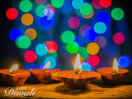 colourful lightings: Happy Diwali - Diya lamps lit with bokeh background during diwali celebration.