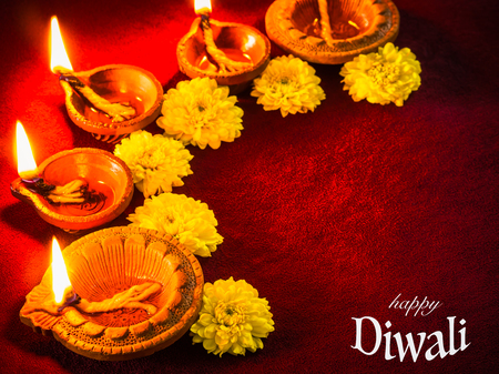 Traditional clay diya lamps lit with flowers for Diwali festival celebration. Stock Photo