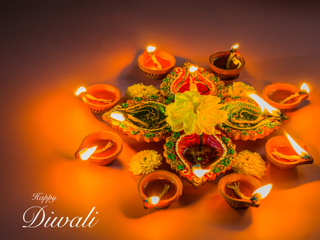 Colorful traditional clay diya lamps with yellow flowers, with selective focus. Stock Photo