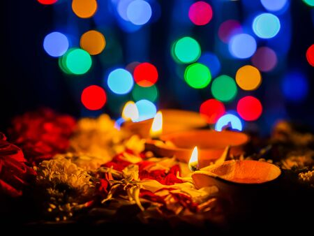 Happy Diwali - Diya lamps lit with flowers bokeh background during diwali celebration.