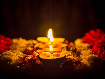 Happy Diwali - Diya lamps lit with flowers during diwali celebration.
