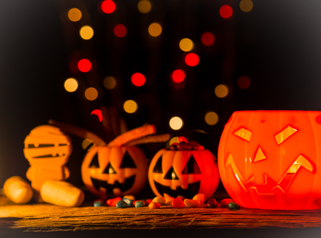 Halloween pumpkin with sweets candies, scary smile. Light inside.