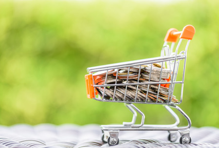 Mini shopping cart with coins in green bokeh background.  Finance and money saving concept.